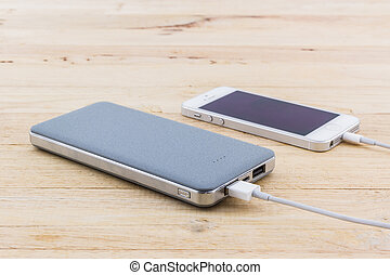 Grey power bank . - Grey power bank on wood background.