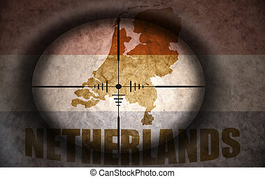 sniper scope aimed at the vintage dutch flag and map
