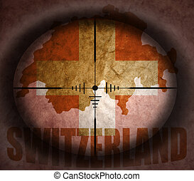 sniper scope aimed at the vintage swiss flag and map