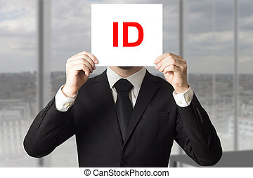businessman hiding face behind sign id - businessman in...