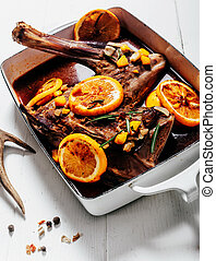 Roast haunch with orange slices and red wine marinade served...