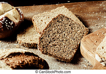 Assorted types of bread on a wooden board - Assorted types...