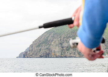 Fisherman using a rod and spinner reel - Fisherman using a...