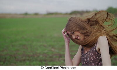 beautiful girl with ribbon in dark dress with floral print run across the green field while wind blowing her hair camera rotate follow from shoes to hair middle shot