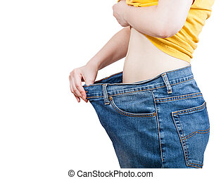 emaciated girl trying on large size old jeans isolated on...