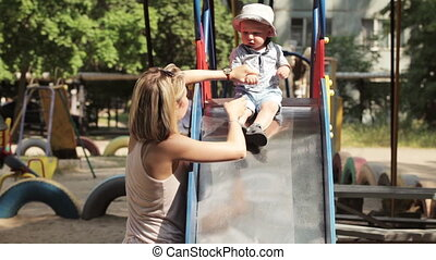 Children slide - Mom with child playing on childrens railway...