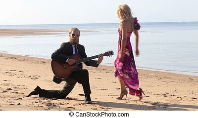 girl dances around bearded guitarist playing on knee