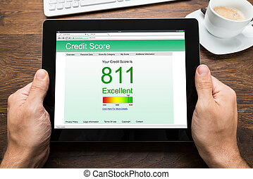 Person Hands With Digital Tablet Showing Credit Score -...