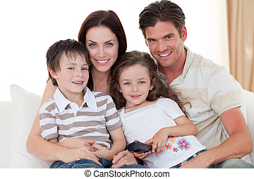 Young family watching TV on the sofa - Smiling Young family...
