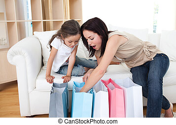 Mother and daughter unpacking shopping bags - Happy Mother...