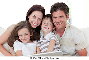 Smiling family using a laptop on the sofa