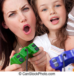 Excited mother and her daughter playing video games at home