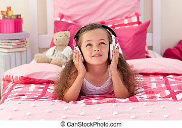 Cute girl listening music in the bedroom - Cute little girl...