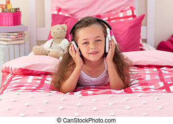 Little girl listening music and lying on bed