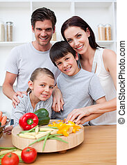 Portrait of happy parents cooking with their children -...
