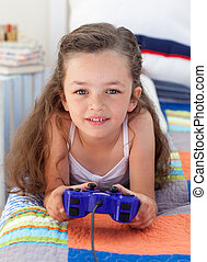 Little girl playing video games and lying on bed