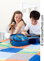 Brother and sister having fun with a guitar in the bedroom