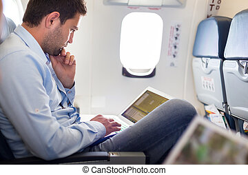 Businessman working with laptop on airplane. - Casually...
