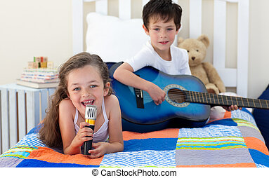Siblings singing and playing guitar on bed - Young siblings...