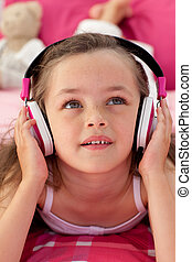Close-up of a little girl listening music - Portrait of a...
