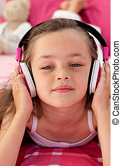 Close-up of a little girl listening music with headphones