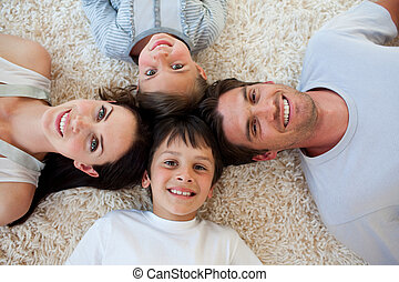 Happy family lying on the floor with heads together
