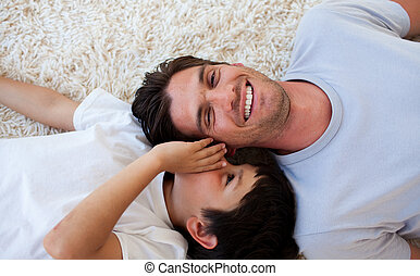 Smiling little boy and his father talking and lying on the...