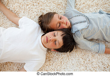 Siblings lying on the floor with heads together