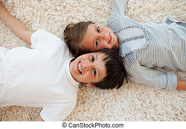 Brother and sister lying on the floor