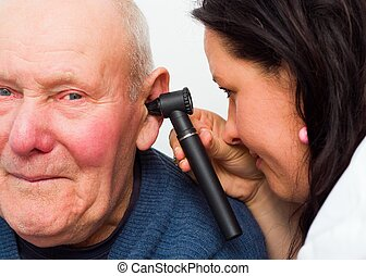 Going To The Audiologist - Audiologist checking elderly mans...