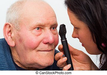 Optical Exam - Optician checking elderly patients cataracts...