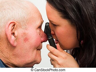 Ophthalmologist At Work - Ophthalmologist examining elderly...