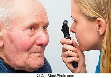 At The Opticians - Optician consulting elderly patient with...