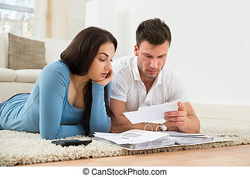 Worried Young Couple Calculating Their Bills At Home