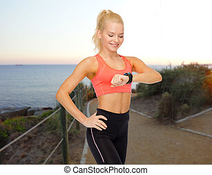 smiling woman looking at heart rate watch outdoors -...