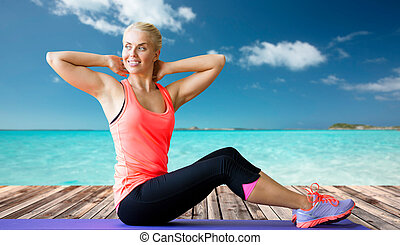 smiling woman doing sit-up on mat over sea - fitness, sport,...