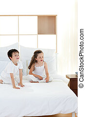 Brother and sister having fun in parent\'s bedroom - Smiling...