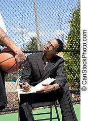 Basketball Coaching - A confident coach speaking to one of...