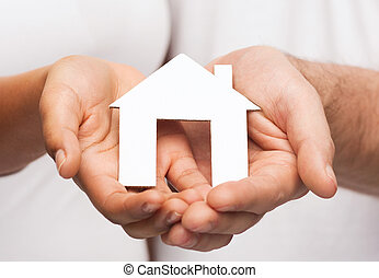 couple hands with paper house - real estate and family...
