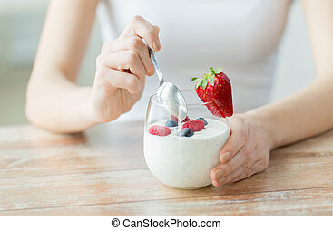 close up of woman hands with yogurt and berries - healthy...