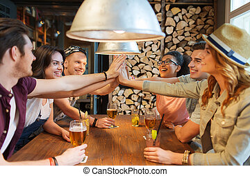 happy friends with drinks making high five at bar - people,...