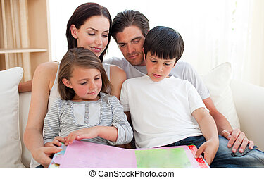 Parents and their children reading a book on the sofa -...
