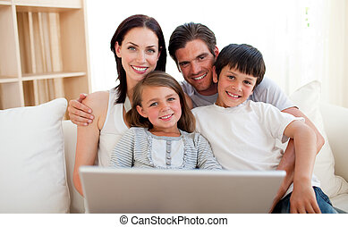 Happy family surfing the internet on the sofa