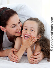 Little girl and her mother having fun on bed together