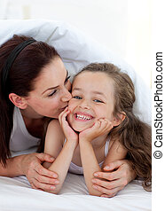 Mother kissing her daughter lying on bed
