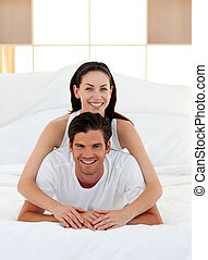 Young couple having fun on bed together Concept of love