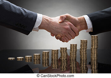 Businessmen Shaking Hands With Coins - Close-up Of Two...
