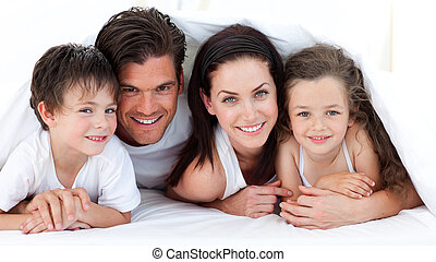 Portrait of a smiling family lying on bed in parent\'s...