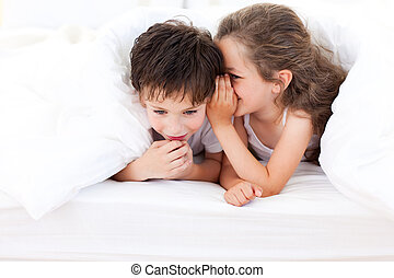 Little girl telling a secret to her brother lying on bed