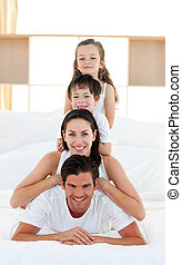 Family having fun on parent\'s bed